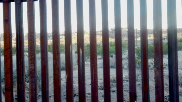 the tall iron fence or wall that borders the united states and mexico in the chihuahua desert near el paso texas and ciudad juarez - surrounding wall stock videos & royalty-free footage