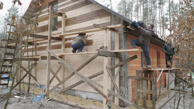 the team of builders are building the house outside the city. - wood stain stock videos & royalty-free footage