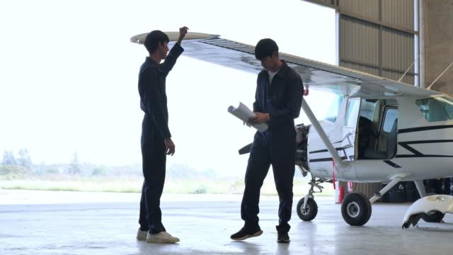vídeos de stock, filmes e b-roll de o técnico planeja e realiza o reparo da aeronave dentro do coletor de aeronaves. - veículo aéreo
