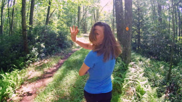 The teenage 16-years-old Caucasian white, long-haired, girl hiking on the forest trail, looking back and waving.