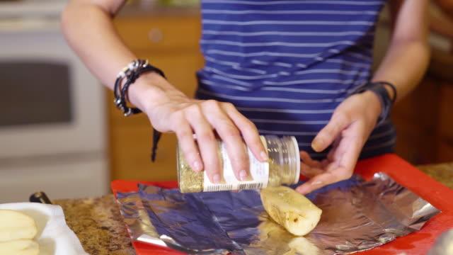 Tonåriga flickan förbereder potatis för bakning.