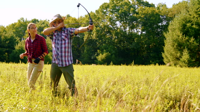 the teenager daughter teaches his father to shoot a bow - archery bow stock videos and b-roll footage