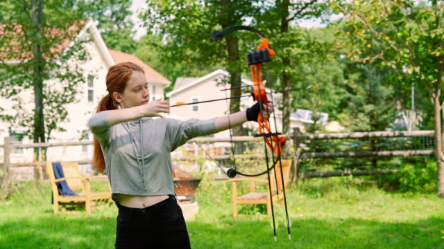 the teenager girl shooting a bow, practicing archery at the backyard - archery bow stock videos and b-roll footage