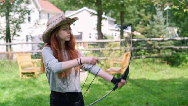 stockvideo's en b-roll-footage met het tiener meisje schieten van een boog, het beoefenen van boogschieten op de achtertuin - 14 15 jaar