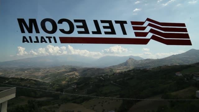 vidéos et rushes de the telecom italia logo is seen on a public payphone, operated by telecom italia spa, against the backdrop of the italian countryside in brittoli,... - événement de la pga