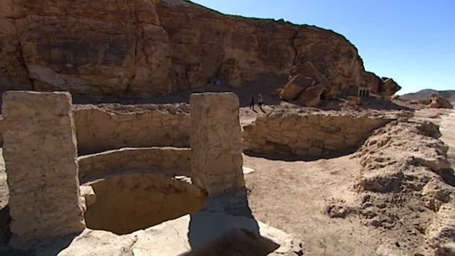 the temple of seti i at kanais. view of an ancient roman well outside the temple which is cut into the rockface in the distance. - felswand stock-videos und b-roll-filmmaterial