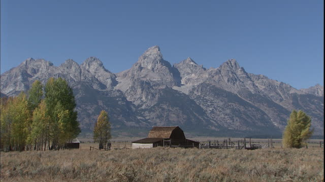 the teton range mountains tower over a ranch. - wyoming ranch stock videos & royalty-free footage