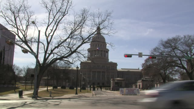 the texas state capitol building intermittent cars passing through frame on street fg tx - texas state capitol building stock videos & royalty-free footage