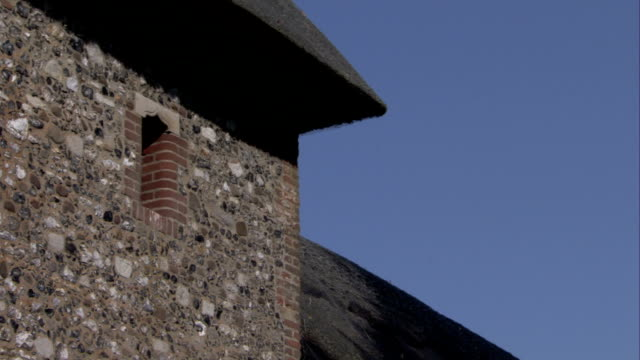 a the thatched roof of st mary's chruch stands out against a blue sky. available in hd. - thatched roof stock videos & royalty-free footage