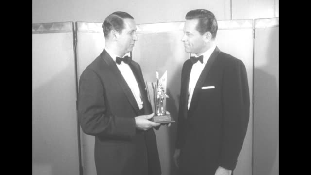 The Theatre Owners of American present William Holden the 1956 Star of the Year award / Myron N Blank gives Holden the award / tilt up of men and...