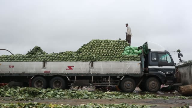 The Thiri Mingala market stands in Yangon Myanmar on Monday Oct 12A laborer tosses a cabbage off a truck at the Thiri Mingala market in...