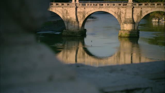 the tiber river flows under rome's ancient ponte sant'angelo. - テベレ川点の映像素材/bロール