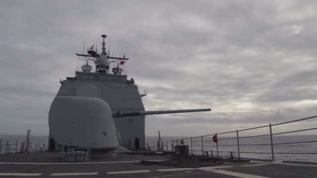 The Ticonderogaclass guidedmissile cruiser USS Lake Champlain fires its forward MK 45 5inch gun during a live fire event Lake Champlain is currently...