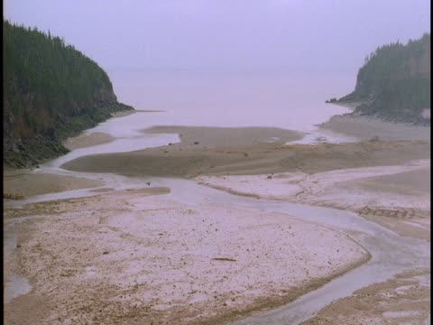 The tide washes over a sandy beach on the Bay of Fundy.