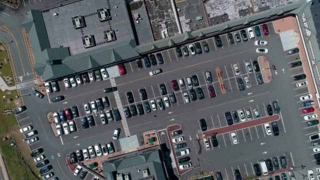 the time-lapse aerial video of the traffic at the parking lot of the shopping mall in the small american town - parking stock videos & royalty-free footage