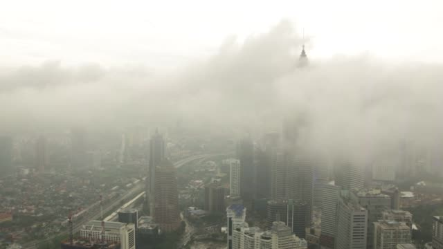 the tips of the petronas twin towers are seen emerging above the clouds in kuala lumpur malaysia shots of the kuala lumpur's skyline as clouds... - newly industrialized country stock videos and b-roll footage