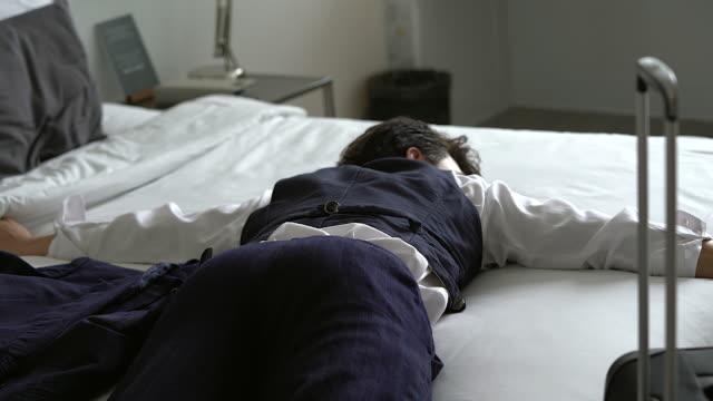 die müdigkeit der junge geschäftsmann arbeiten im bett mit einem laptop vor ihm. asiatischen schön geschäftsmann mit müdigkeit im bett zu schlafen. - exhaustion stock-videos und b-roll-filmmaterial