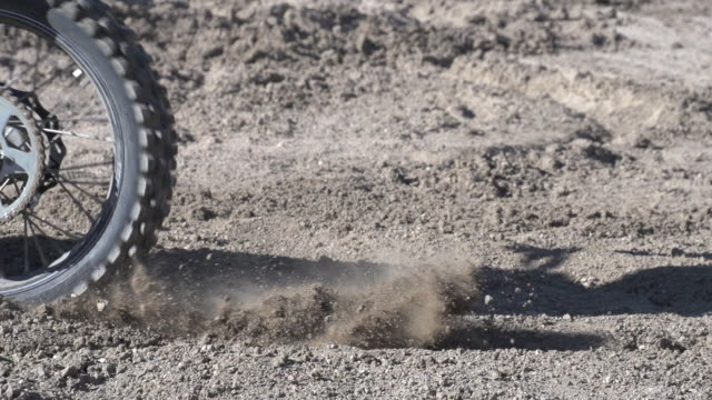 the tires from a motocross dirt motorcycle spinning out in the dirt.  - super slow motion - filmed at 240 fps - soil stock videos and b-roll footage