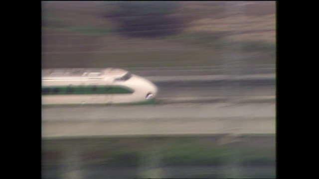 The Tohoku Shinkansen bullet train speeds past farms and buildings in the Japanese countryside.