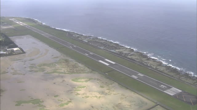 the tokunoshima airport runway follows the coast of tokunoshima island, japan. - campo d'aviazione video stock e b–roll