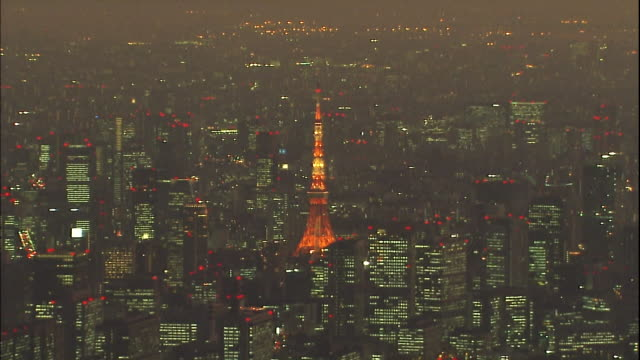 the tokyo skytree tower and surrounding high rise buildings light up the night sky. - broadcasting stock videos & royalty-free footage