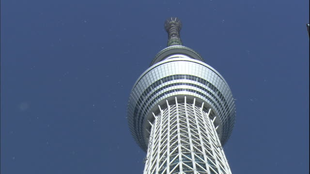 the tokyo skytree towers observation deck extends outward near the top. - aufnahme von unten stock-videos und b-roll-filmmaterial