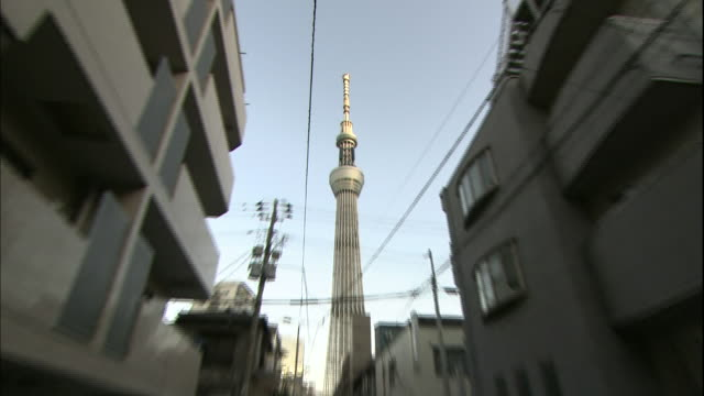 the tokyo skytree towers over a neighborhood alley. - aufnahme von unten stock-videos und b-roll-filmmaterial