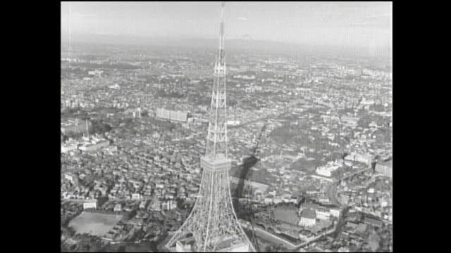 the tokyo tower casts a shadow on an adjacent neighborhood. - showa period stock videos & royalty-free footage