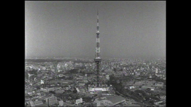 the tokyo tower dominates the skyline above shiba park. - showa period stock videos & royalty-free footage