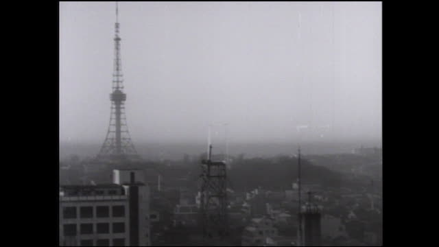 the tokyo tower is the tallest structure near high-rise buildings in the shiba park area of tokyo. - 1962 stock videos and b-roll footage