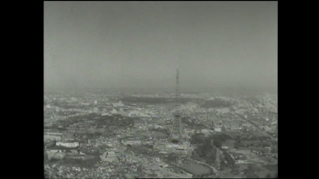the tokyo tower juts up from the center of tokyo, japan. - tokyo tower stock videos and b-roll footage