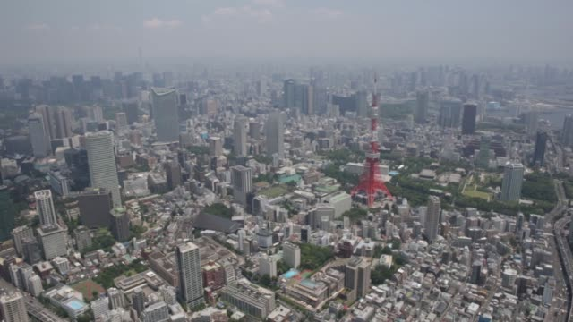 The Tokyo Tower left stands amid buildings in this aerial photograph taken in Tokyo Japan on Wednesday June 24 2015