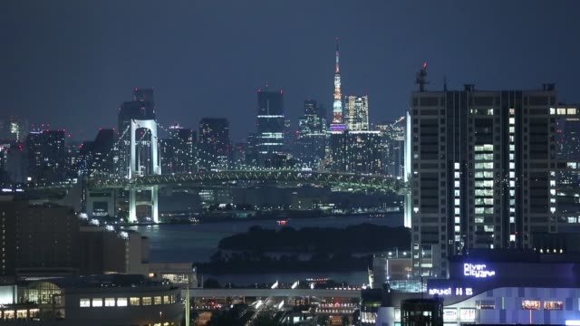 the tokyo tower right and the rainbow bridge center stands illuminated at night in tokyo japan on wednesday aug 10 2016 - natural arch stock videos & royalty-free footage