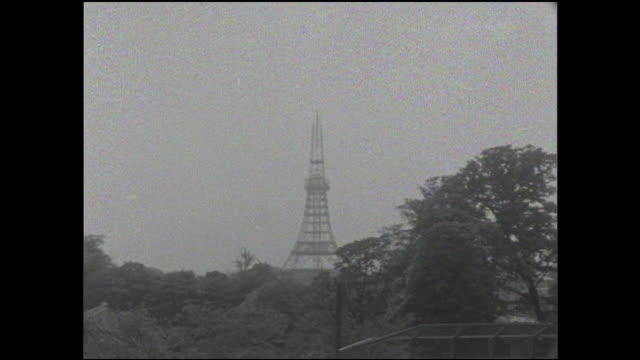 the tokyo tower, under construction, towers above a park. - mast stock videos & royalty-free footage