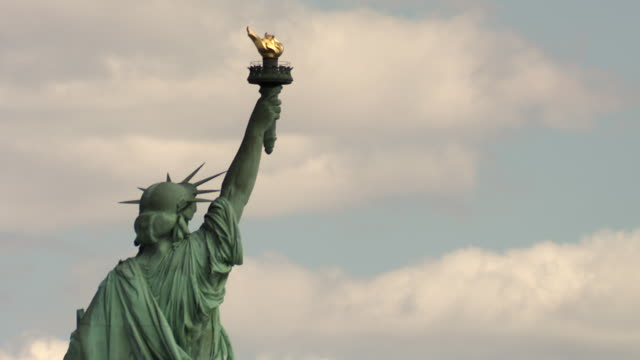 vídeos de stock e filmes b-roll de the top third of the statue of liberty including her tunic, crown and torch taken from her back. - statue of liberty new york city