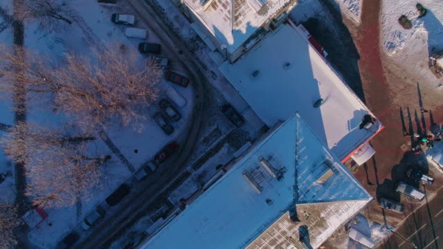 the top view, directly above aerial view on the residential district of the winter city covered by snow. climbing and spinning complex camera motion. - stationary stock videos & royalty-free footage