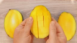 The top view of the hands cutting a fresh ripe mango half cut into the cubes