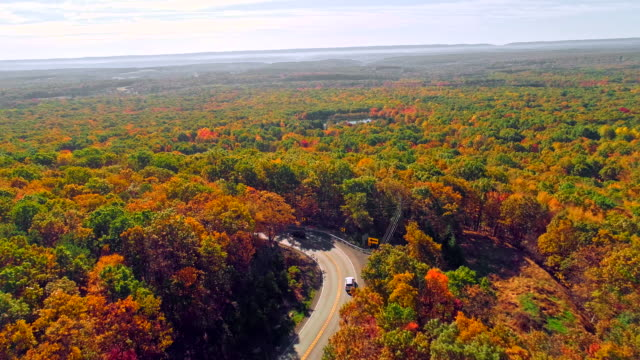 Het bovenaanzicht op de weg in de bergbos in Appalachian, Poconos, Pennsylvania, met fall gebladerte. Luchtfoto drone video.