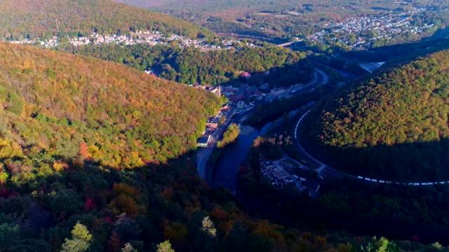 Die Draufsicht auf der Straße in den Bergwald in Appalachian, Poconos, Pennsylvania, mit Herbstlaub. Luftbild-Drohne Video.
