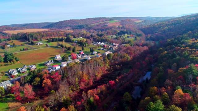 vídeos de stock, filmes e b-roll de a vista superior na estrada na pequena cidade de kunckletown, poconos, na pensilvânia, com folhagem de outono. vídeo do zangão aéreo. - cena rural