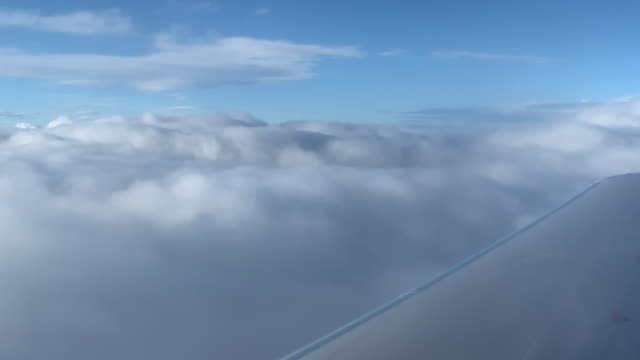 the tops of clouds from over the wing of an airliner jet on a sunny day - cumulonimbus stock videos & royalty-free footage