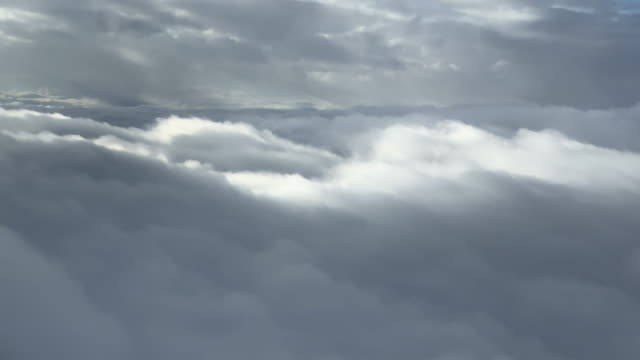 the tops of grey storm clouds while flying through them (view from aircraft) - cumulonimbus stock videos & royalty-free footage