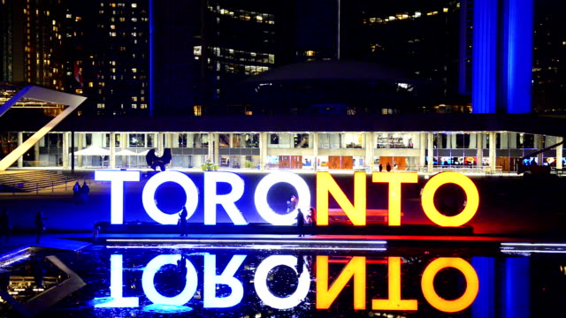 the toronto sign lights in the colors of the french flag after the terror attacks to paris in honor of the innocent victims and in support of the... - 光栄点の映像素材/bロール