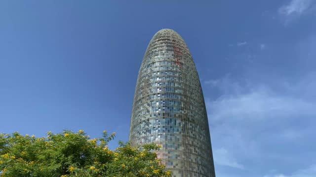 the torre glòries, formerly known as torre agbar (catalan pronunciation: [ˈtorə əɡˈbaɾ]), is a 38-story skyscraper located between avinguda diagonal and carrer badajoz, near plaça de les glòries catalanes, which marks the gateway to the new techno - spanish culture stock videos & royalty-free footage