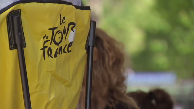 the tour de france to finish in paris with chris froome wearing the yellow jersey shows exterior shots people buying memorabilia from a tour de... - ツール・ド・フランス点の映像素材/bロール