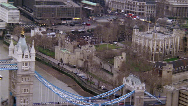 the tower bridge crosses the river thames and leads to the famous tower of london. - tower of london stock videos & royalty-free footage