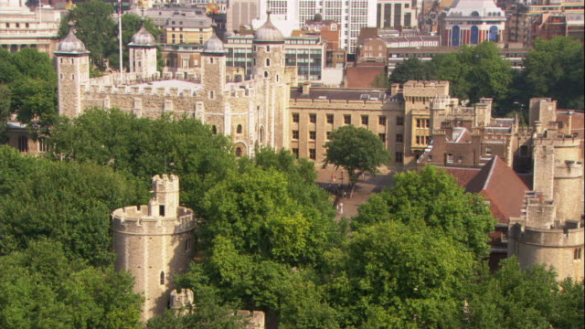 the tower of london and the gherkin tower above treetops and rooftops in london. - tower of london stock videos & royalty-free footage