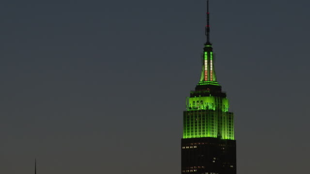 the tower of the empire states building is illumined with green.  a catch light goes round and round on top of the tower. - st. patrick's day stock videos & royalty-free footage