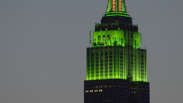 the tower of the empire states building is illumined with green.  the green lights slowly change color. - st. patrick's day stock videos and b-roll footage