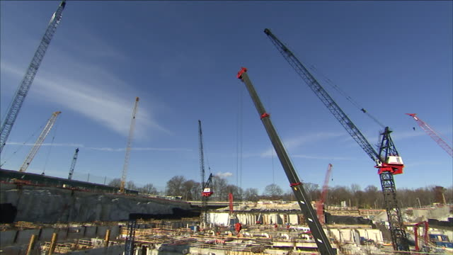 the towers of construction cranes dominate a construction site. - hoisting stock videos & royalty-free footage